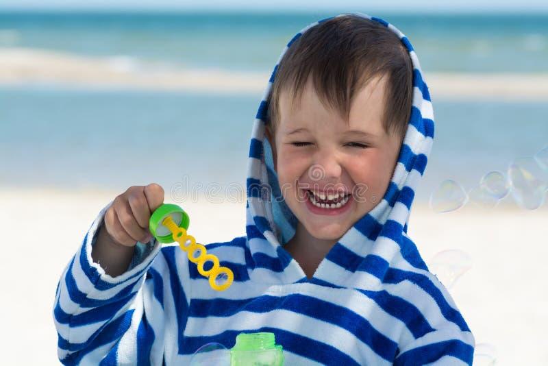 Ein kleines nettes Kind in einer gestreiften Robe brennt Blasen vor dem hintergrund des Meeres und einer gewaschenen Borte durch  stockfotos