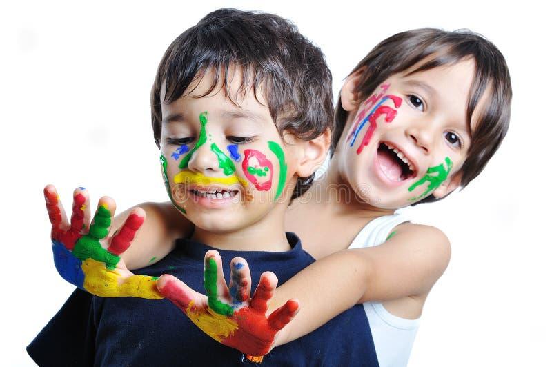 Ein kleines nettes Kind mit einigen Farben stockbilder