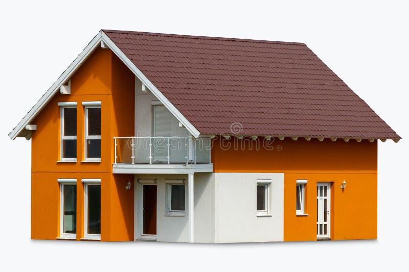 Ein kleines orange Haus mit weißen Fenstern und einem dunkelbraunen Metalldach neues Haus auf dem Rasen lizenzfreie stockfotografie