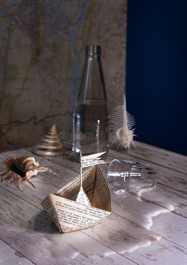 Ein kleines Papierboot in einer Wasserpfütze lizenzfreie stockfotografie