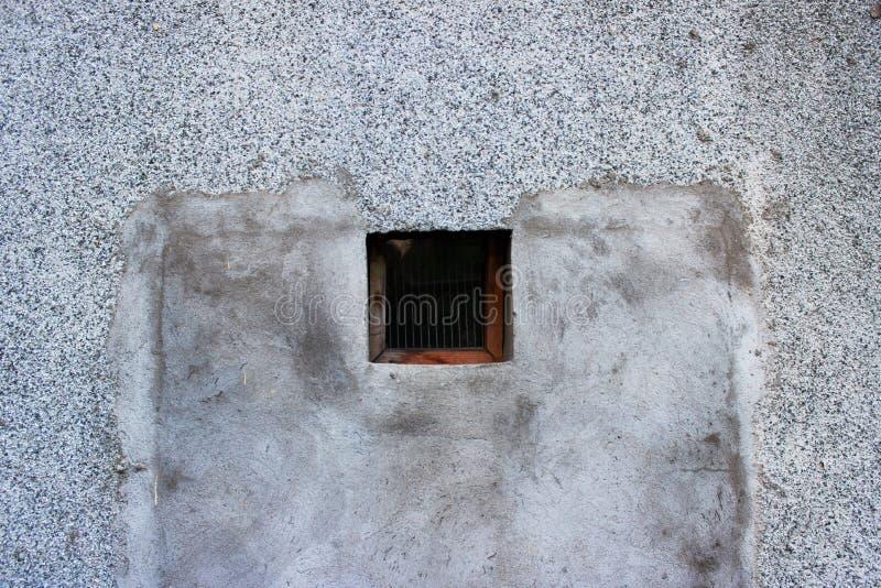 Ein kleines quadratisches Fenster mit einem Holzrahmen, der zu den Keller, bedeckt mit feinem Gitter und Glas führt lizenzfreie stockbilder