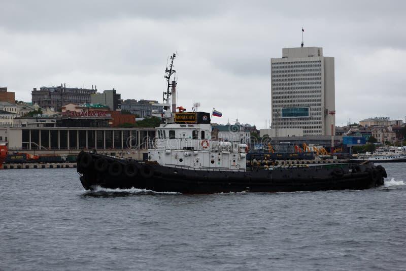 Ein kleines schleppendes Boot ist auf ruhigem Wasser lizenzfreies stockfoto