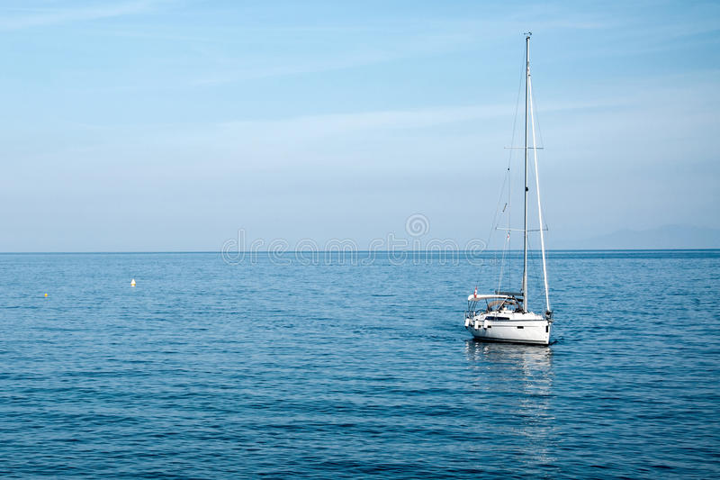 Ein kleines Segelboot machte vor der Küste, im Hintergrundmeer fest lizenzfreie stockfotografie