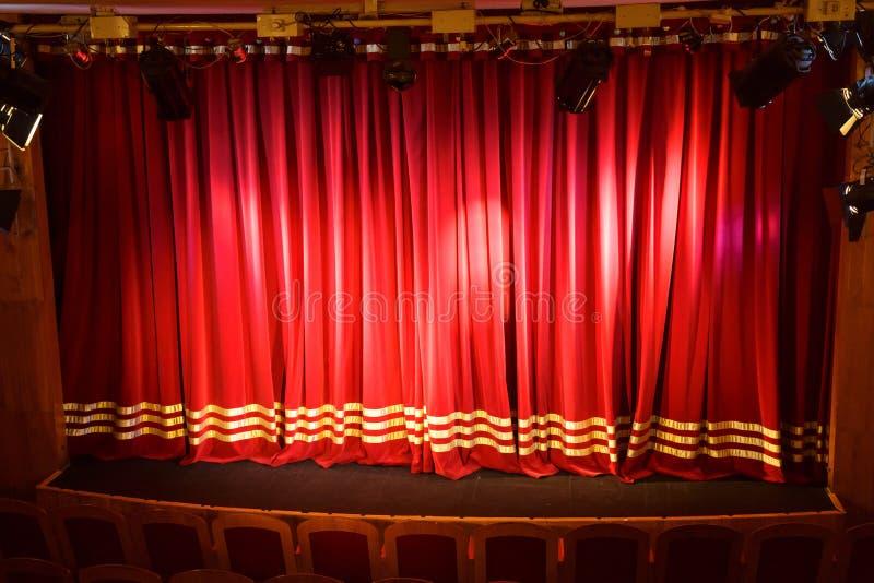 Ein kleines Stadium geleuchtet mit den Scheinwerfern geschlossen durch einen roten Vorhang lizenzfreie stockbilder