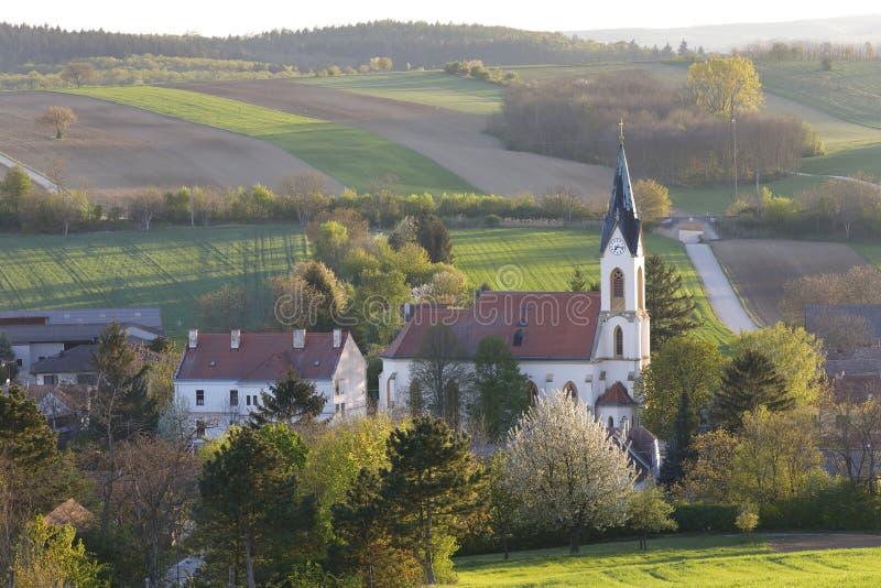 Ein kleines Tal und seine Gemeindekirche im Ackerland in Niederösterreich, Weinviertel stockbild