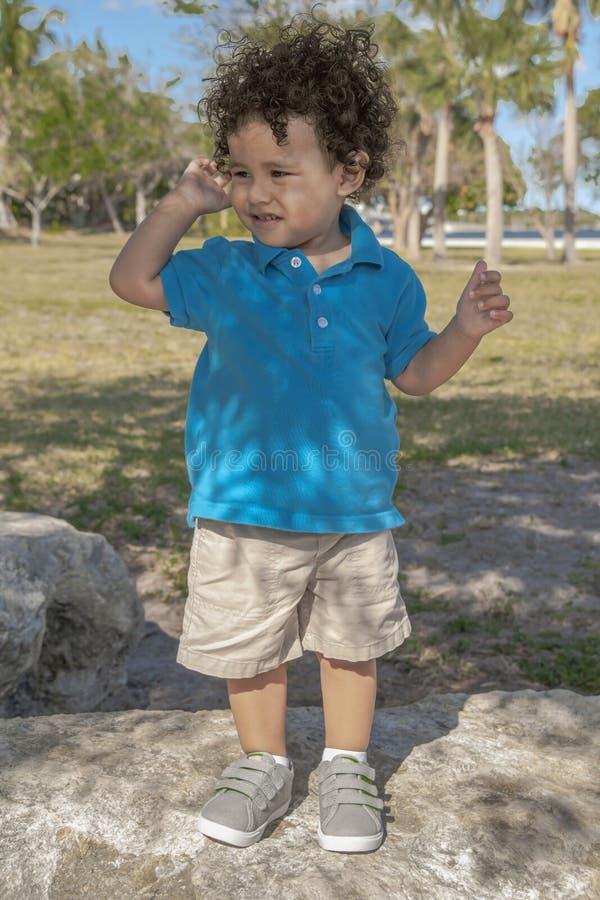 Ein Kleinkind auf einen großen Felsen an den Parkblicken rechts sein lizenzfreies stockbild