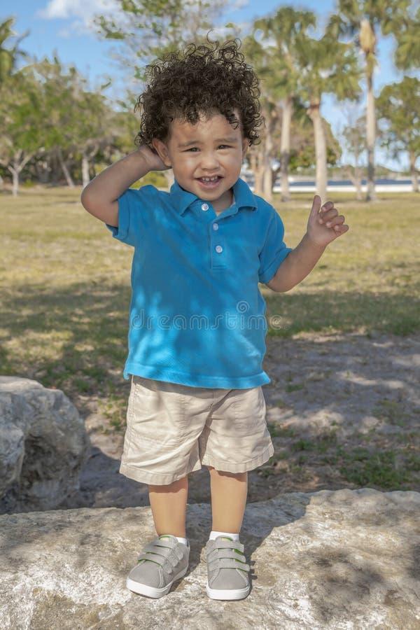 Ein Kleinkind steht nach einem großen Felsen am Park, der die Kamera betrachtet lizenzfreie stockbilder