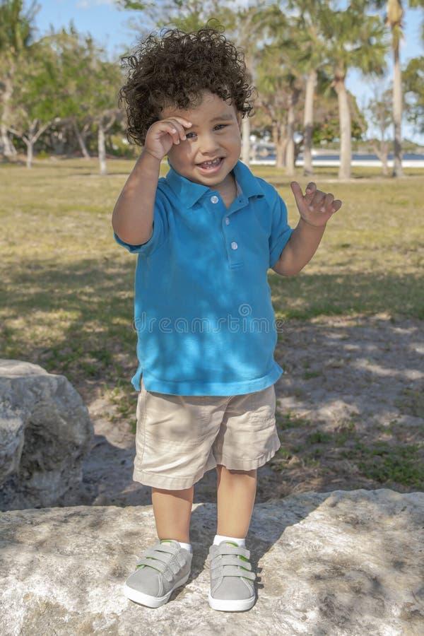 Ein Kleinkind steht nach einem großen Flussstein am lokalen Park stockbilder