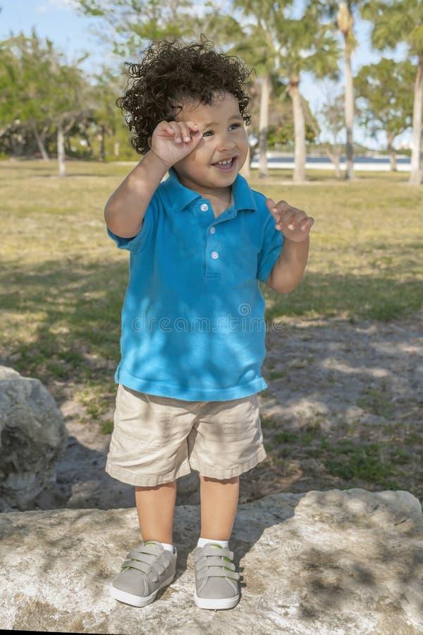 Ein Kleinkind steht oben auf einem Flussstein am Gemeinschaftspark lizenzfreie stockbilder