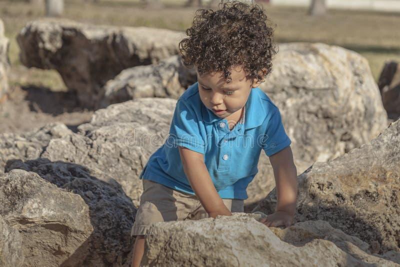 Ein Kleinkindjunge geht sorgfältig durch einige große Felsen stockbild