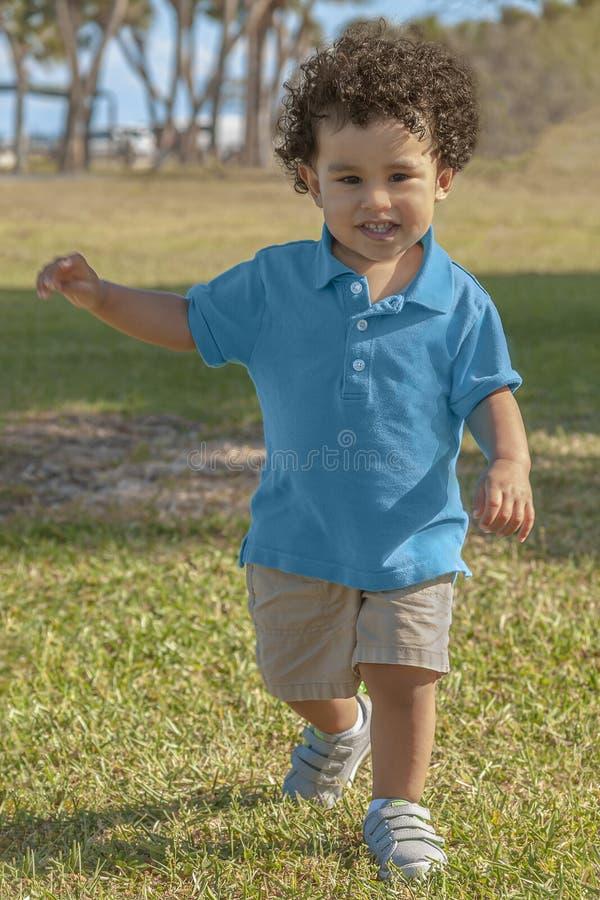 Ein Kleinkindjunge lernt, auf seine Selbst an einem Florida-Park zu gehen lizenzfreie stockfotografie