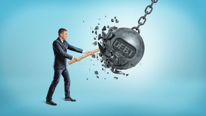 Ein Kleinunternehmer zertrümmert einen riesigen schwingeisenball mit einem Wort SCHULD auf ihm unter Verwendung eines Hammers lizenzfreie stockfotografie