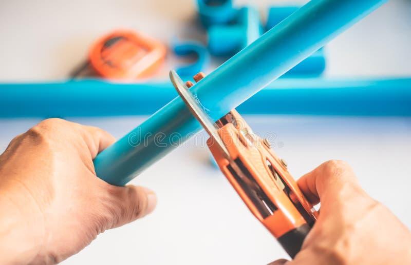 Ein Klempner schnitt PVC-Rohr mit PVC-Rohr, das Zangenwerkzeug schneidet Selektiver Fokus Plombieren von Reparatur und von Wartun lizenzfreie stockfotografie