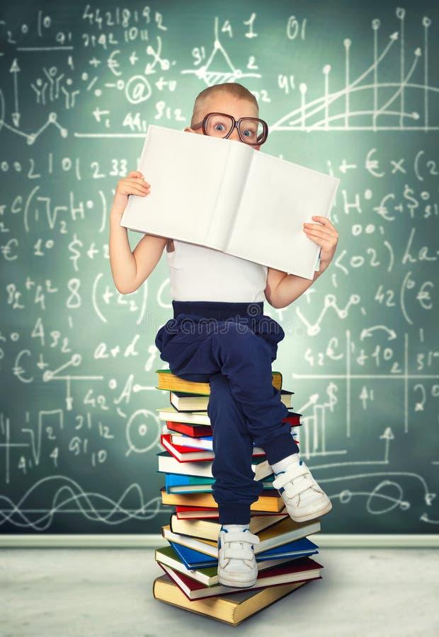 Ein kluger Junge mit Gläsern sitzt und liest Bücher Ein kleiner Wissenschaftler stockfotos