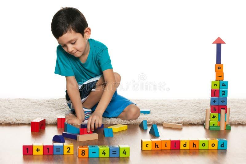 Kluger kleiner Junge mit Spielwaren auf dem Boden stockbilder