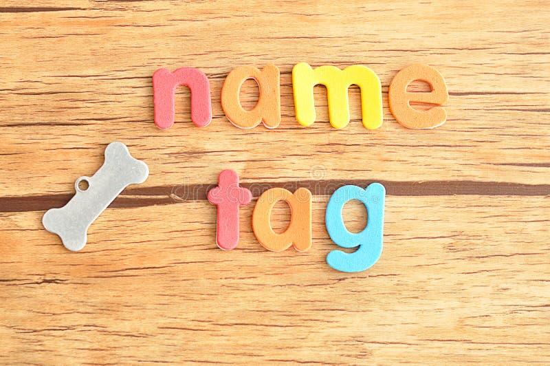 Ein Knochenformnamensschild für einen Hund mit dem Wortnamensschild lizenzfreie stockfotografie