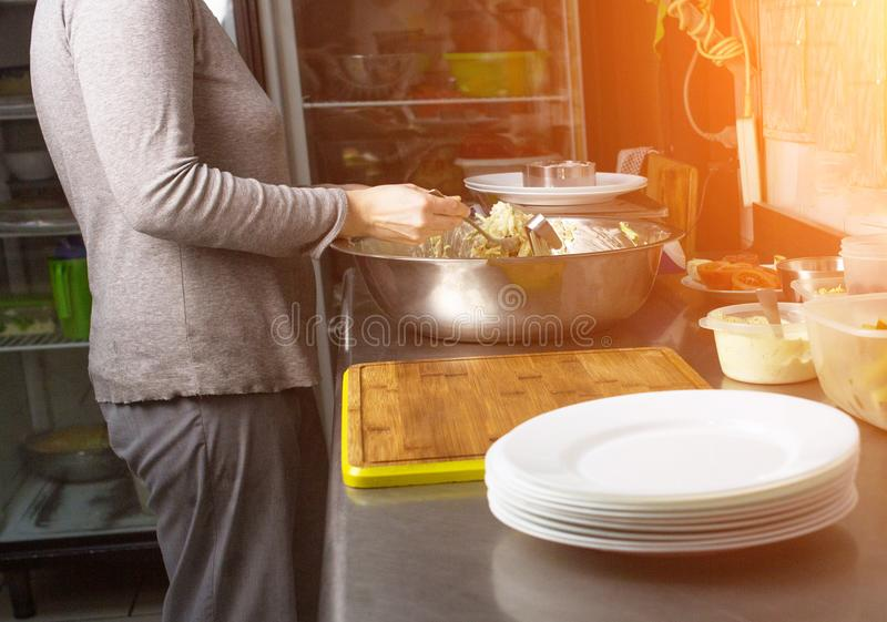Ein Koch in der Küche wiegt Teile Salat auf Skalen in den Gramm und in den Aufschlägen zum Tabelle, kitchener stockfotografie