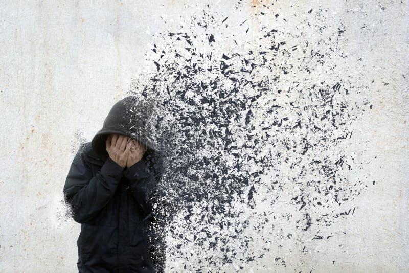 Ein Konzept der psychischen Gesundheit eines mit Kapuze Mannes, der seinen Kopf in seinen Händen hält Wenn sein Körper weg disolv lizenzfreie stockfotografie