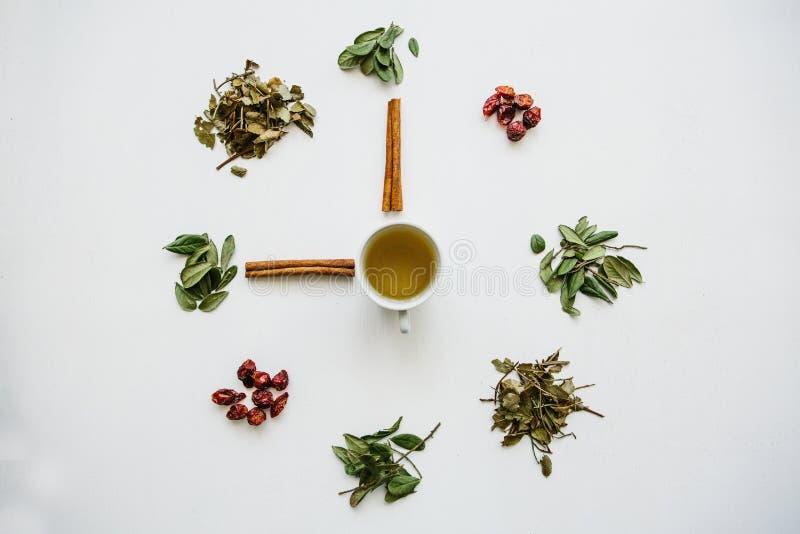 Ein Konzept oder eine kreative Idee, die Teezeit bedeutet Nützlicher Kräuter- oder grüner Tee in der Mitte und um das verschieden lizenzfreie stockfotografie
