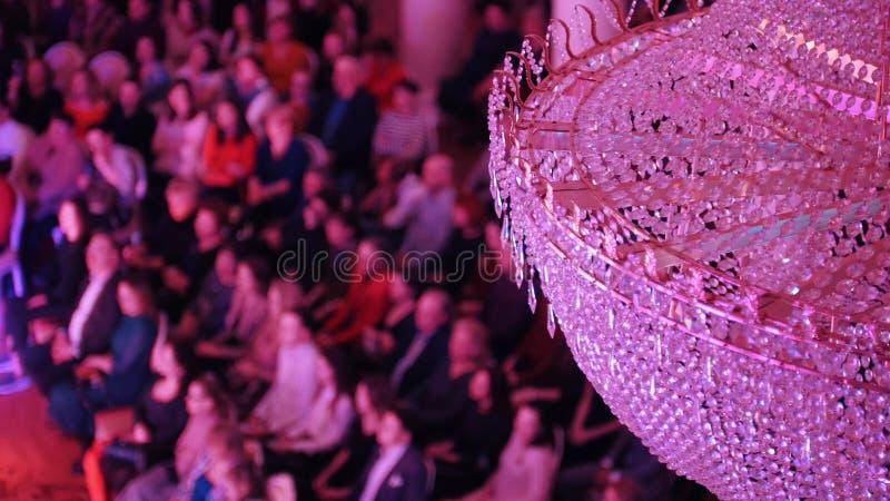 Ein Konzert im Konzertsaal mit einem gro?en Kristallleuchter Leute, die auf den St?hlen sitzen stockbilder
