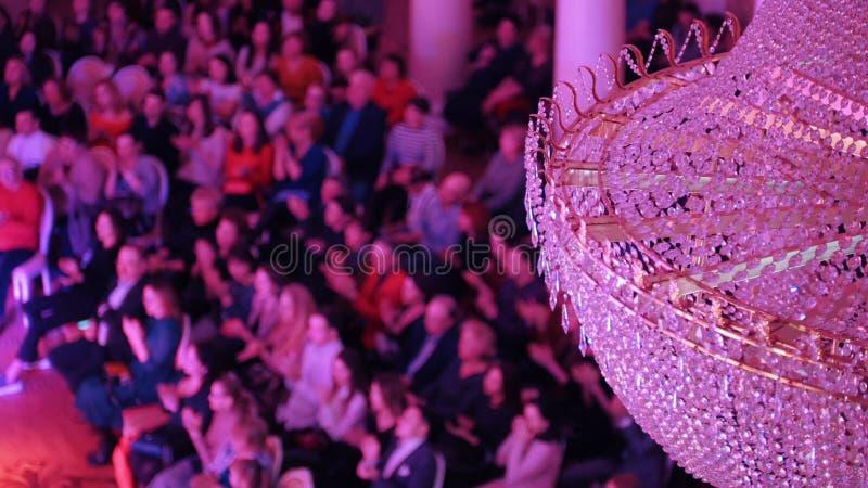 Ein Konzert im Konzertsaal mit einem gro?en Kristallleuchter Leute, die auf den St?hlen sitzen und ihre H?nde klatschen stockfotos