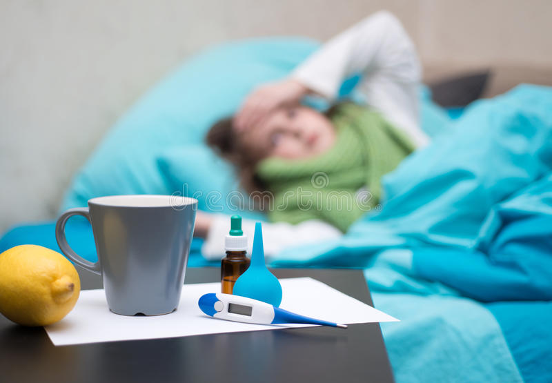 Ein krankes Baby, das im Bett vor ihrem Gesicht liegt, mischt Drogen bei lizenzfreie stockbilder