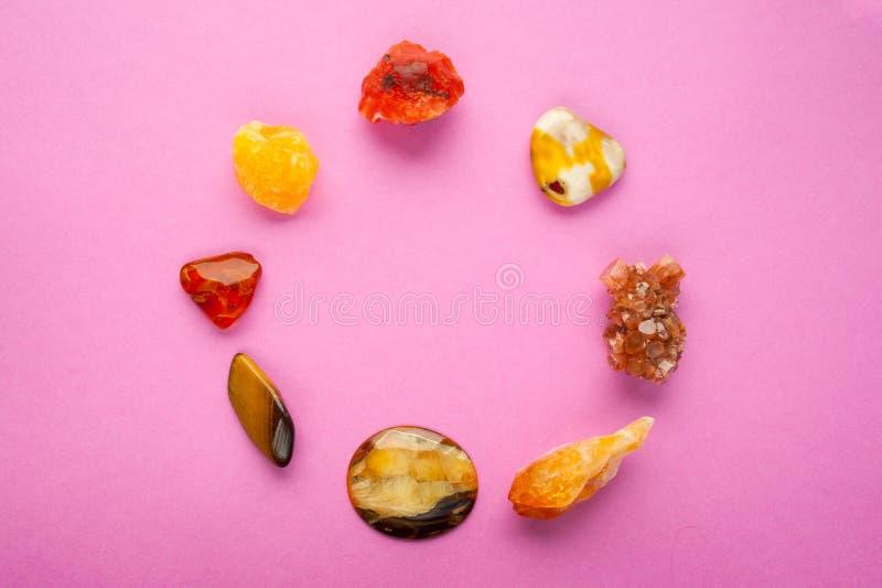 Ein Kreis von verschiedenen Mineralien auf rosa Hintergrund Geistiger Bernstein, Kalzit, Aragonite, Simbercite, Jaspis, Tigerauge lizenzfreie stockbilder