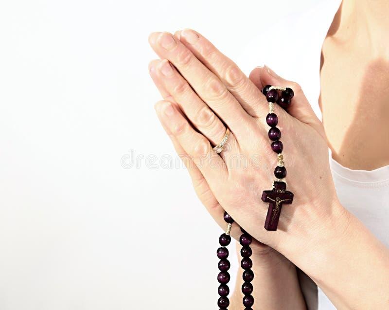 Ein Kreuz mit Rosenkranzperlen haltene und betende Frau stockfotografie