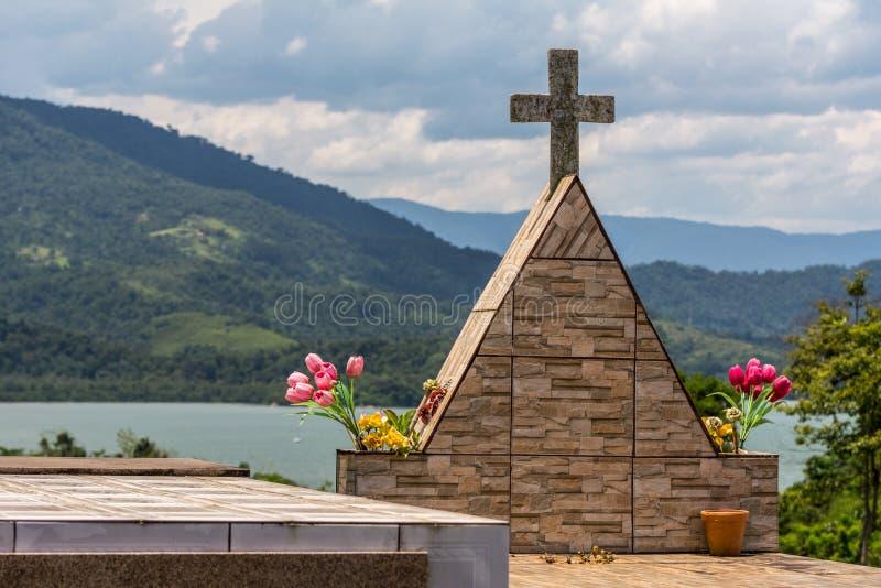 Ein Kreuz und das tomstone eines Grabs im Kirchhof in Paraty, Brasilien, mit dem Meer an der Rückseite stockfoto