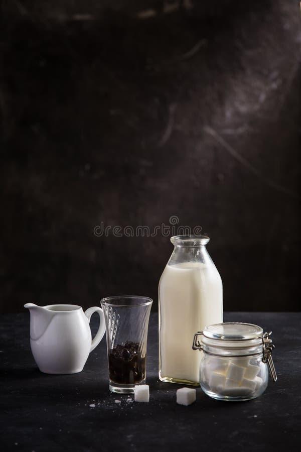 Ein Krug/eine Flasche von Milch, von Glas der Blase und von Zuckertopf auf schwarzer Tabelle stockbilder