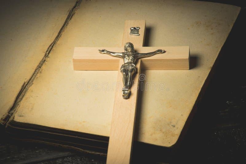 Ein Kruzifix vor dem hintergrund eines offenen Buches lizenzfreie stockbilder
