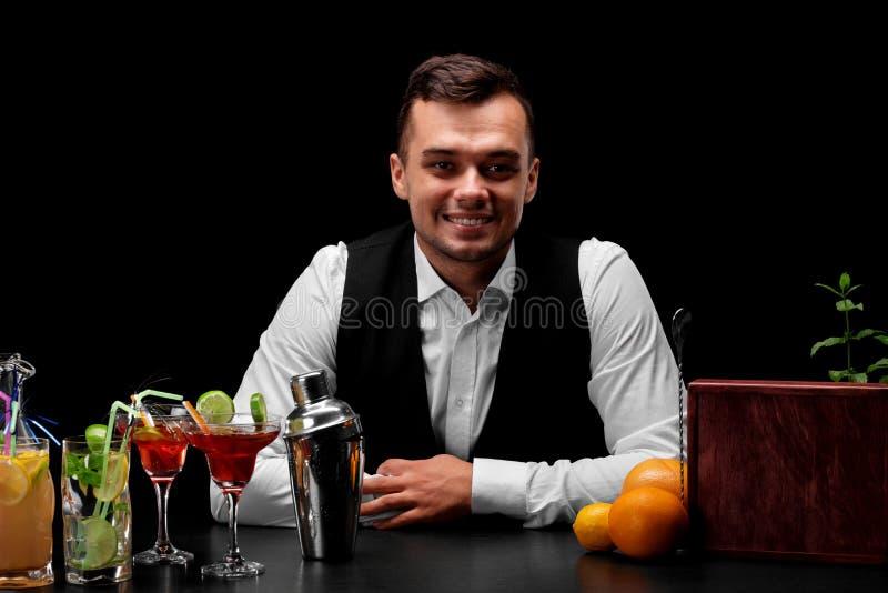 Ein lächelnder Barmixer, der hinter einem Stangenzähler auf einem schwarzen Hintergrund steht Restaurantservice und Unterhaltungs stockbilder