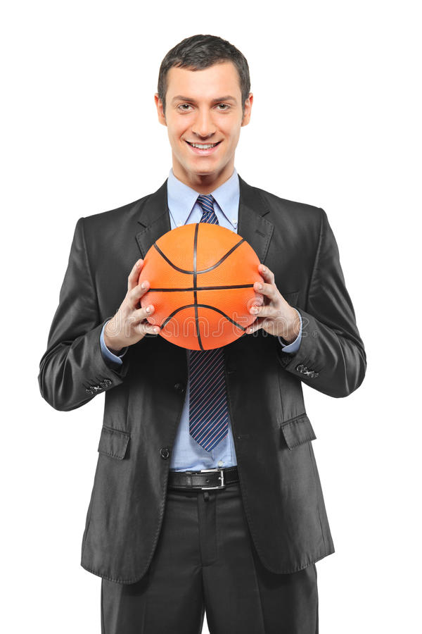 Ein lächelnder Geschäftsmann, der einen Basketball anhält stockfoto