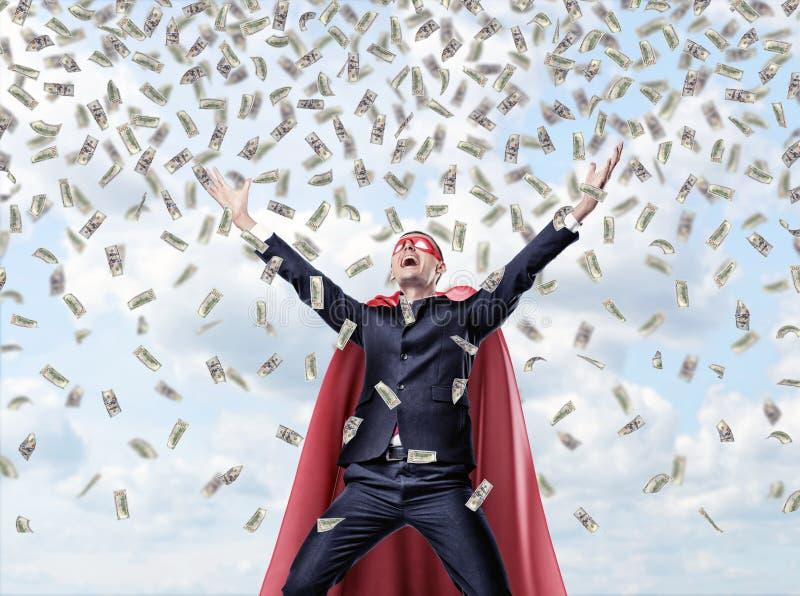 Ein lächelnder Geschäftsmann in einem roten Kap des Superhelden mit den Händen hob in Erfolgsbewegung unter Geldwasserfall an stockbilder