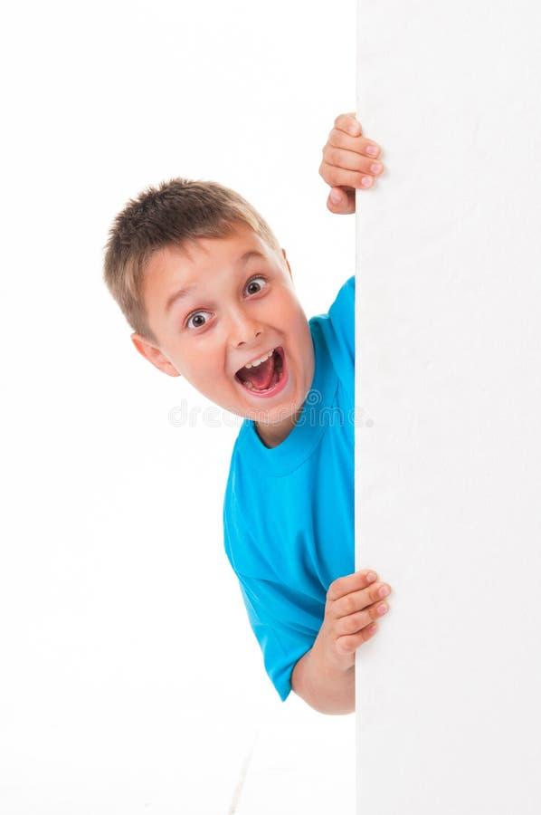 Ein lächelnder hübscher Mann, der hinter einer weißen Platte lokalisiert auf weißem Hintergrund aufwirft lizenzfreie stockbilder
