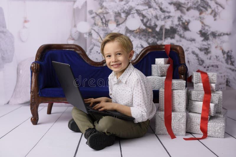 Ein lächelnder Junge als Santa Claus mit einem Weihnachtsbaum im Hintergrund stockfotos