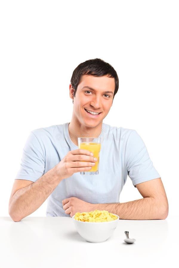 Ein lächelnder junger Mann am Frühstück stockbilder