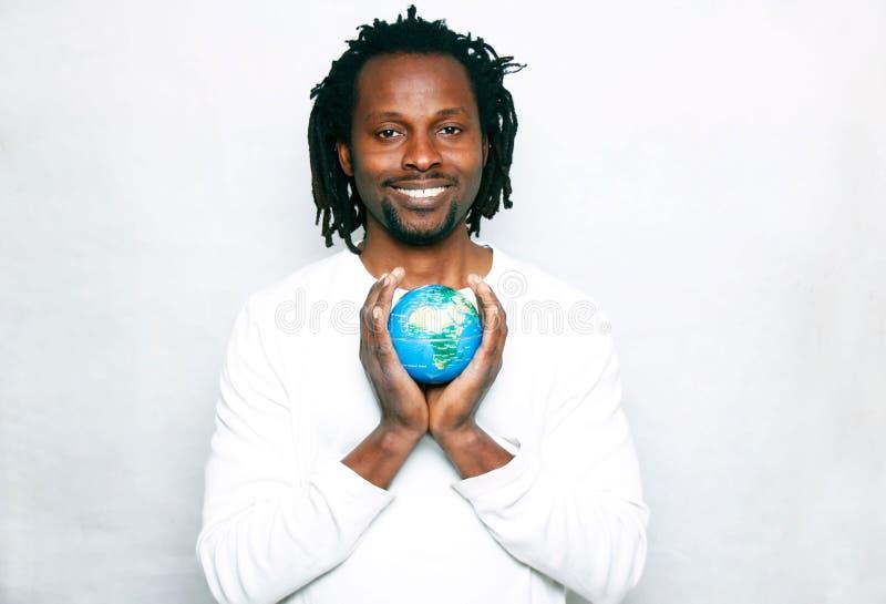 Ein lächelnder junger Mann hält die Weltkugel in seinen Händen lizenzfreies stockbild