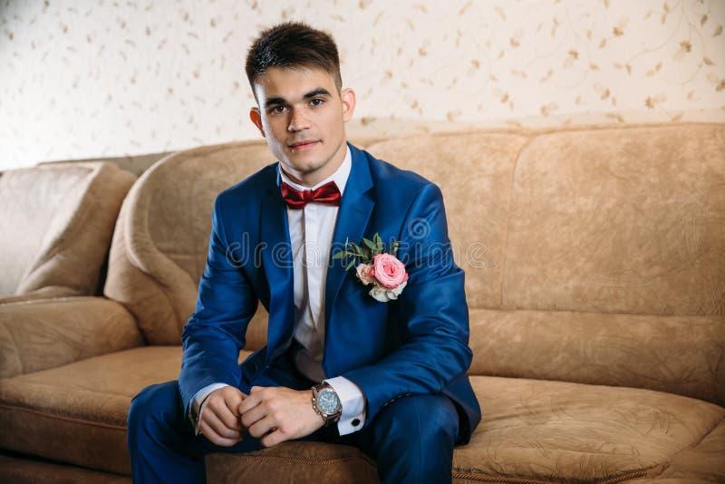 Ein lächelnder Kerl in einer schönen Klage sitzt auf der Couch Er kleidete in einem weißen Hemd, in den Manschettenknöpfen, in ei lizenzfreie stockfotografie
