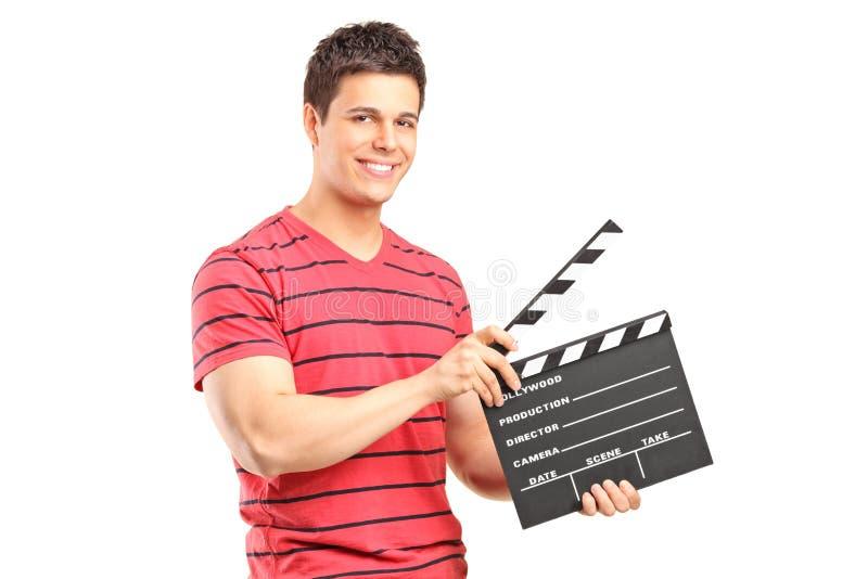 Ein lächelnder Mann, der ein Filmklatschen anhält lizenzfreie stockbilder