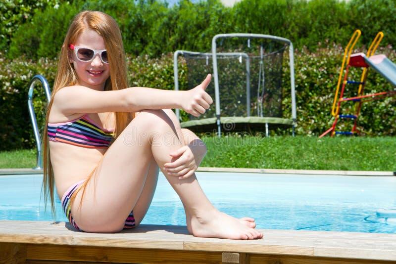 Ein lächelndes kleines Mädchen auf dem Poolside lizenzfreie stockbilder