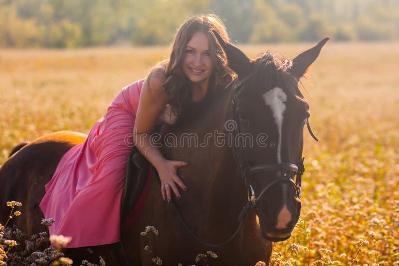 ein lächelndes Mädchen auf einem Pferd in einem Kleid in stockfoto