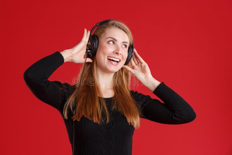 Ein lächelndes Mädchen, hört Musik, in den Kopfhörern und glücklich in lächeln Auf einem roten Hintergrund lizenzfreie stockfotos