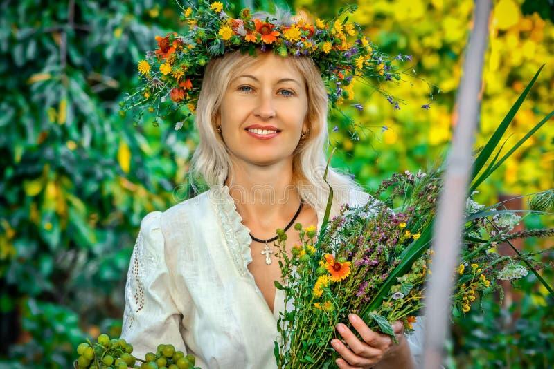 Ein lächelndes schönes Mädchen mit netten Blumen stockbild