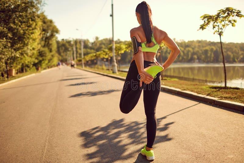 Ein Läufermädchen tut, Beine im Park ausdehnend stockfotografie