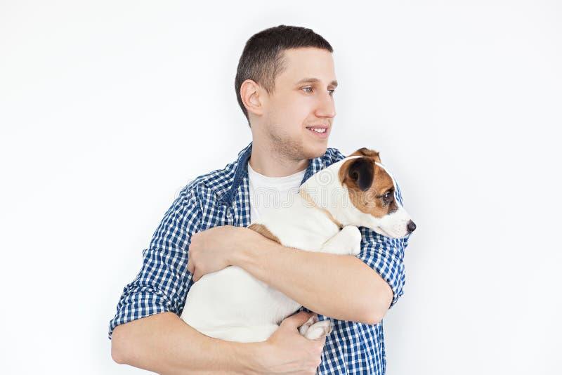 Ein l?chelnder gut aussehender Mann, der einen reinrassigen Hund auf einem wei?en Hintergrund h?lt Das Konzept von Leuten und von stockfotos
