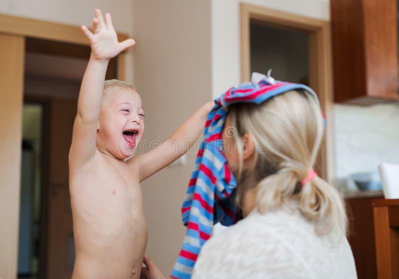 Ein lachender behinderter Down-Syndrom Junge mit seiner Mutter, die zuhause Spaß hat lizenzfreies stockbild