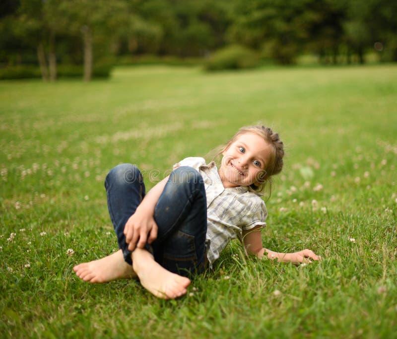 Ein lachendes kleines Mädchen, das auf hellgrünem Gras sitzt stockbilder