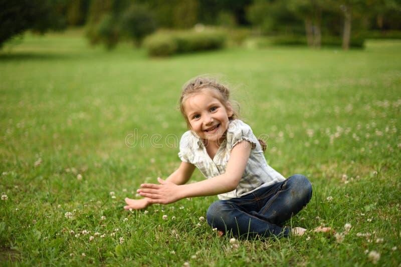 Ein lachendes kleines Mädchen, das auf hellgrünem Gras sitzt stockfotografie