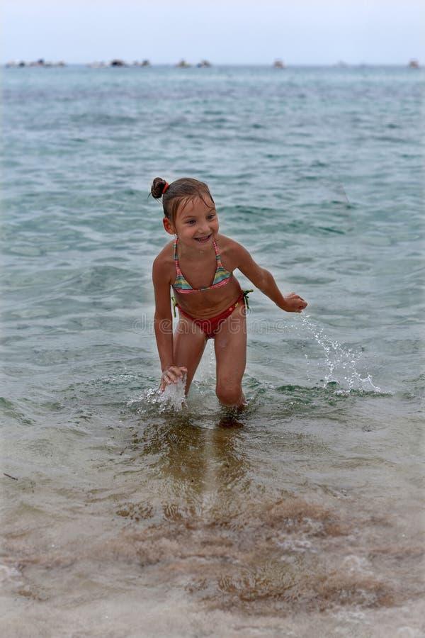 Ein lachendes kleines Mädchen, das in den Meereswellen steht stockbilder